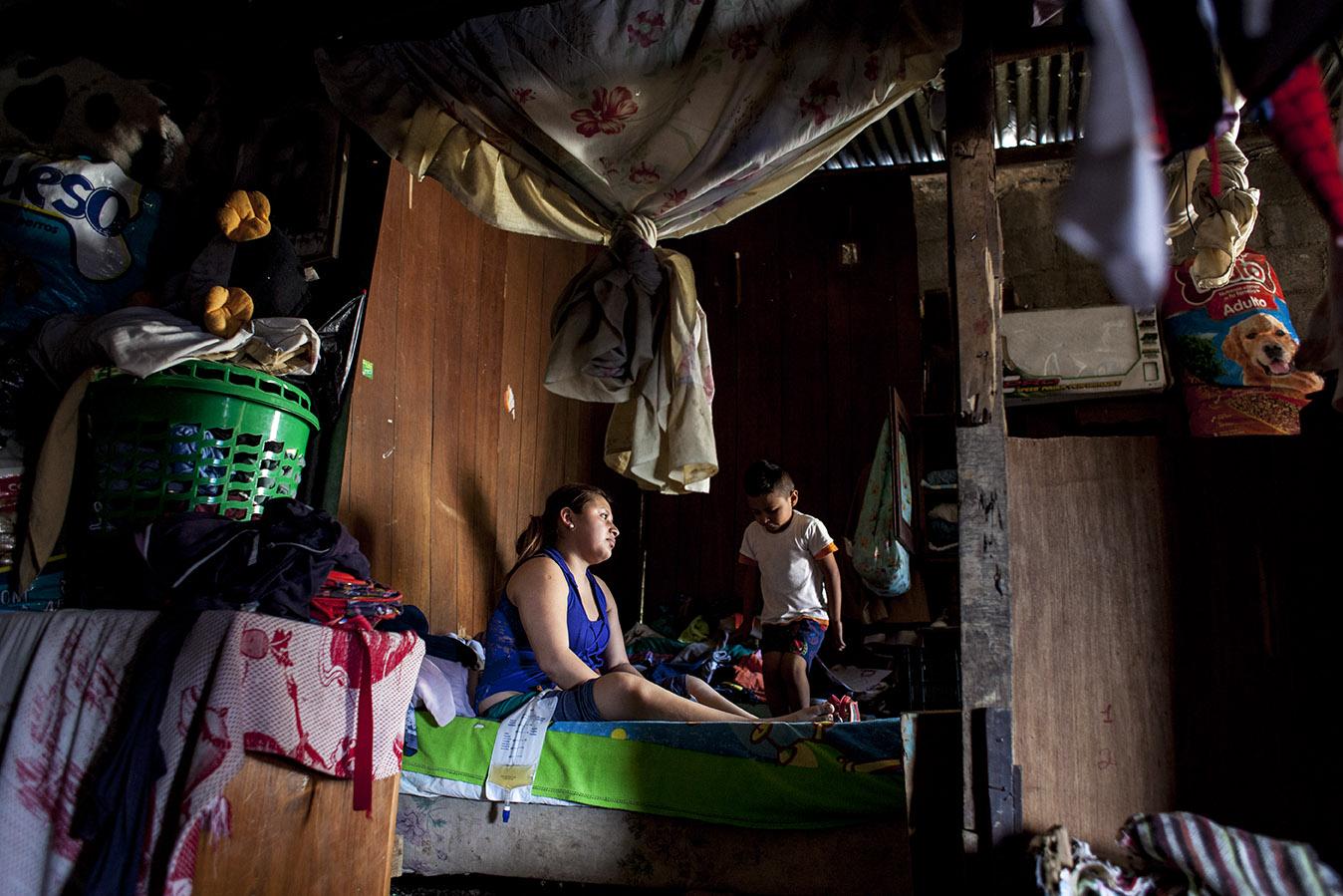 Vivian Flores, 22, mira tele postrada en su cama, mientras su hijo, Kenny, de cinco años, juega brincando a la par suya. Simone Dalmasso